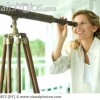 Woman looking through telescope, smiling, close-up