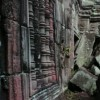 stock-footage-pan-from-pile-of-fallen-temple-sandstone-blocks-to-carved-angkorian-statue-in-red-stone-wall
